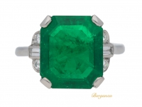 front view Art Deco solitaire Colombian emerald ring with diamond set shoulders, circa 1925.