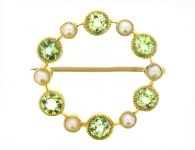 Antique peridot and pearl circle brooch in 15 carat yellow gold, circa 1900.