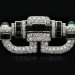 Art Deco onyx, diamond and emerald brooch, circa 1925.