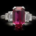 Ruby and diamond flanked solitaire ring, English, circa 2000.