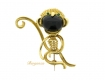 alt='Kutchinsky emerald, onyx and yellow gold monkey brooch, English, circa 1964.'