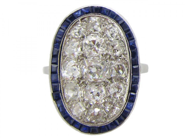 front view Diamond cluster ring with calibré sapphire border, circa 1910.