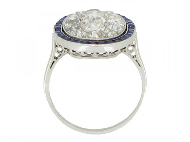back view Diamond cluster ring with calibré sapphire border, circa 1910.