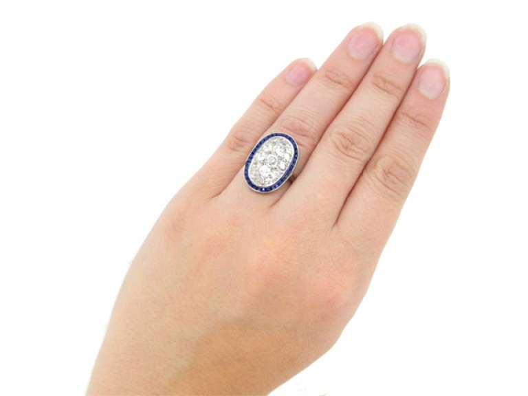 hand view Diamond cluster ring with calibré sapphire border, circa 1910.