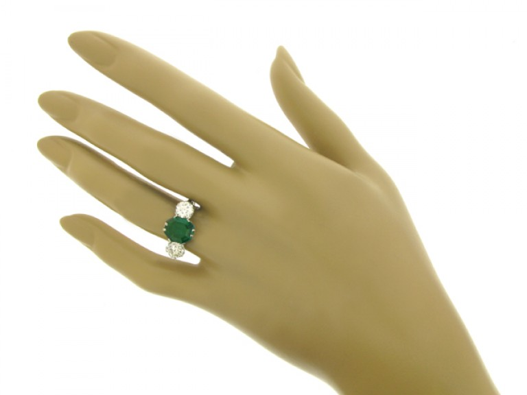 hand view Edwardian old mine emerald and diamond three stone ring, circa 1910.