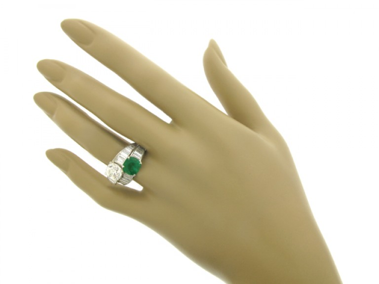 hand veiw Tiffany & Co. emerald and diamond crossover ring, American, circa 1930.