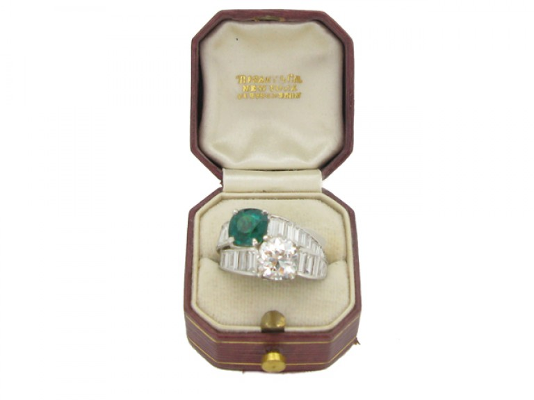 boxed view Tiffany & Co. emerald and diamond crossover ring, American, circa 1930.