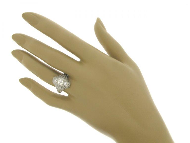 hand view Ornate three stone diamond cluster ring, circa 1920.