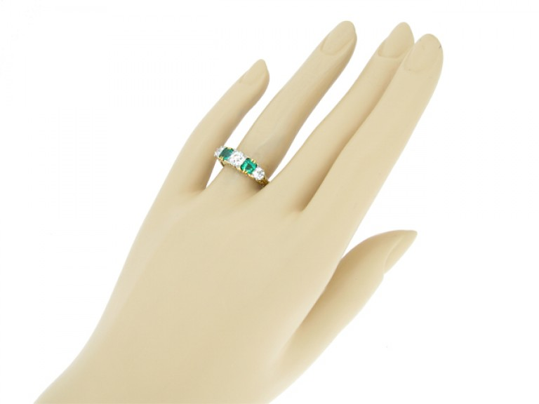 HAND VIEW Carved emerald and diamond five stone ring, circa 1900.