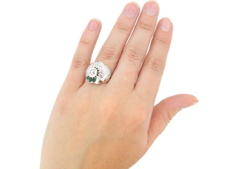 hand view Seaman Schepps vintage diamond and emerald flower ring, American circa 1965.