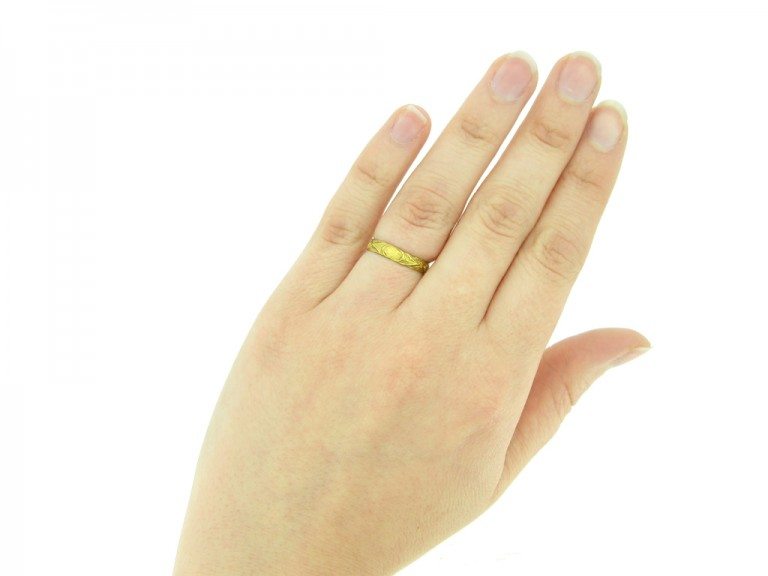 hand view Gold posy ring with carved detailing, 'It is my love'