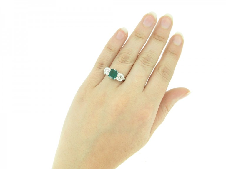 hand view Colombian emerald and diamond three stone ring