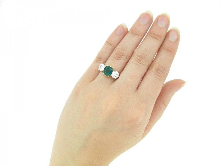 hand view Emerald and diamond three stone ring,