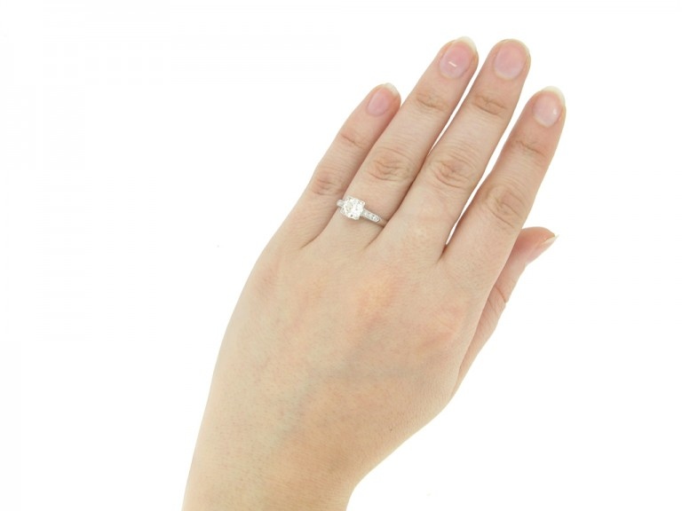 hand view Solitaire diamond engagement ring with diamond set shoulders, circa 1930.