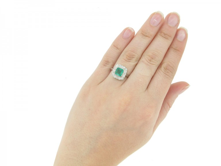 hand view Antique emerald and diamond cluster ring, circa 1915.