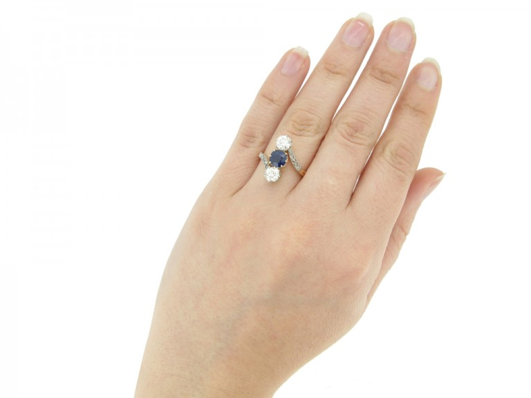 hand view Antique sapphire and diamond three stone cross over engagement ring, circa 1905.