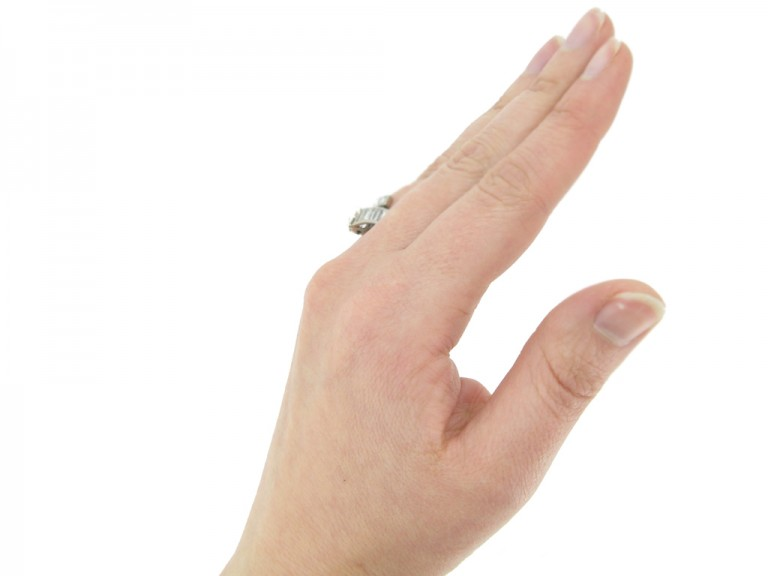 hand view Drop, baguette and square cut diamond ring, circa 1960.